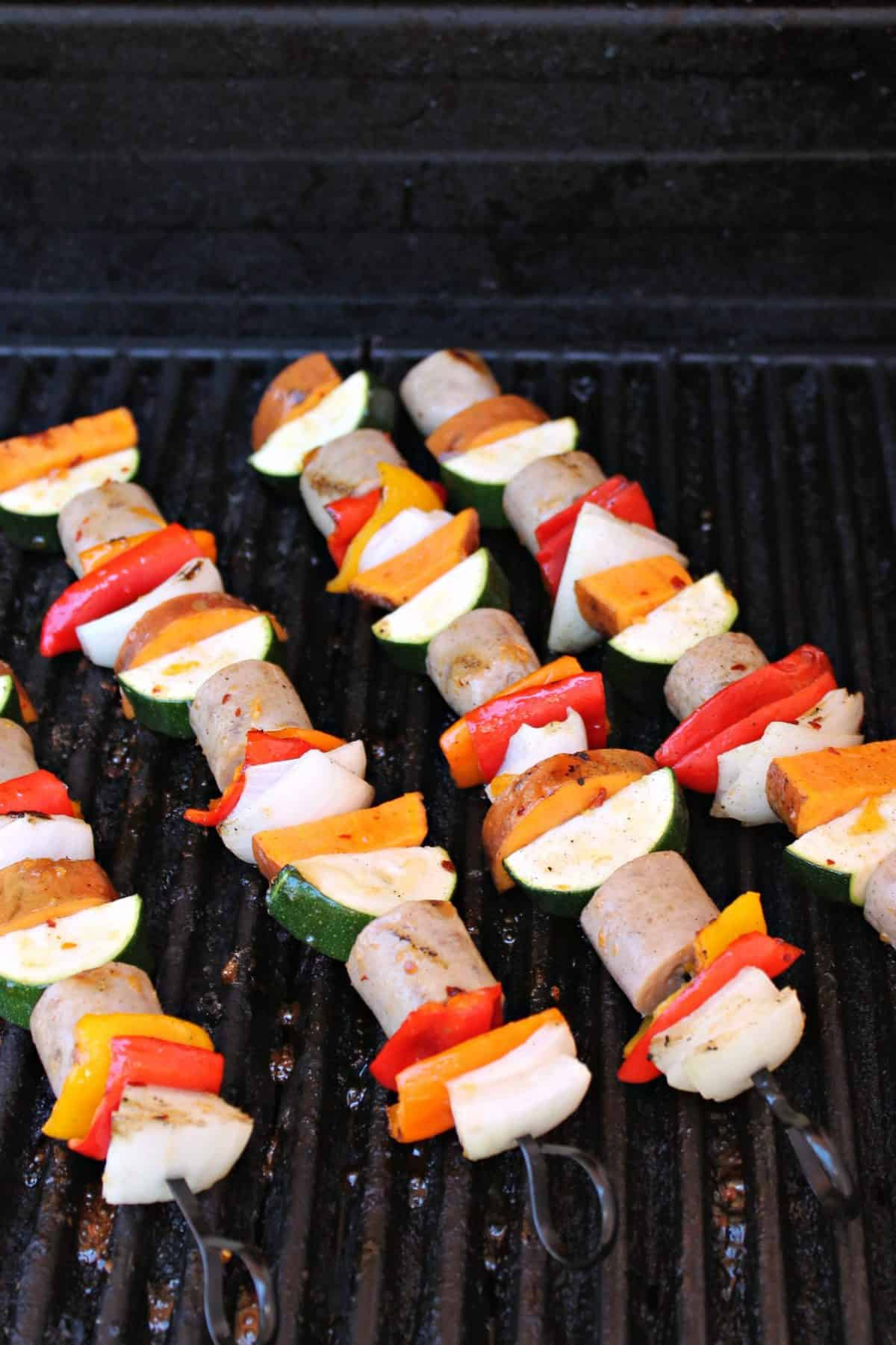 Close up of Glazed Chicken Apple Sausage & Sweet Potato Kabobs cooking on the grill.