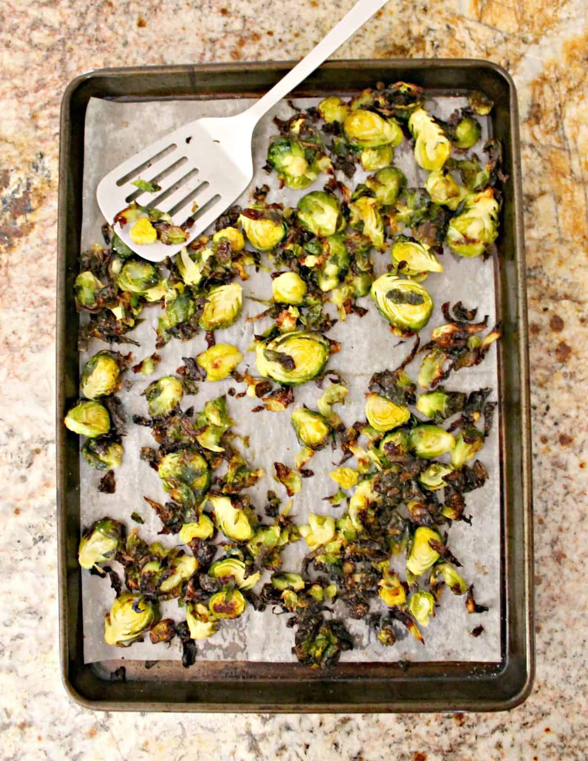 Overhead shot of a pan of roasted Brussels sprouts on a kitchen counter top.