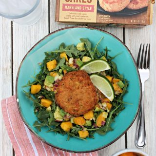 Overhead shot of Crab Cake Salad in a turquoise dish on a picnic table with a napkin, fork, water glass and product box.