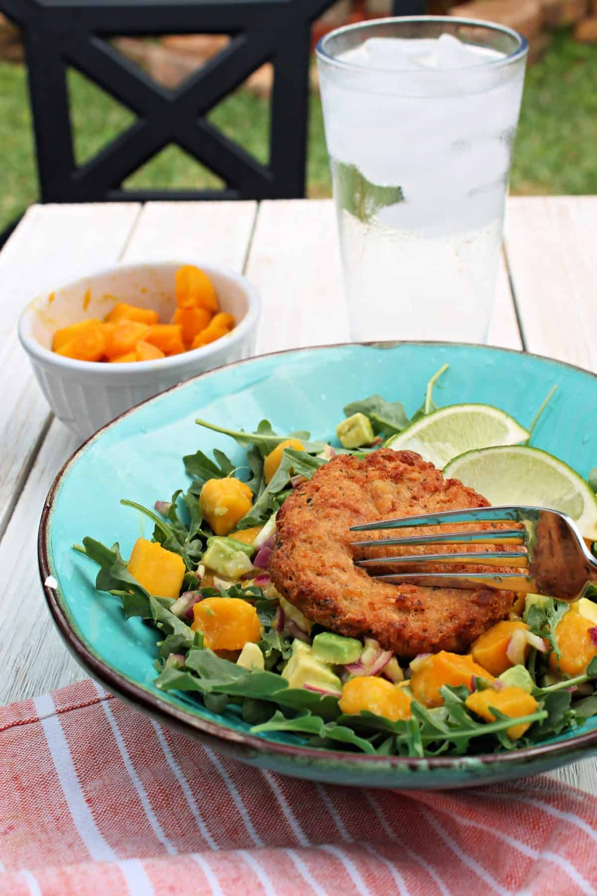 Close up of Crab Cake Salad in a turquoise dish on a picnic table.
