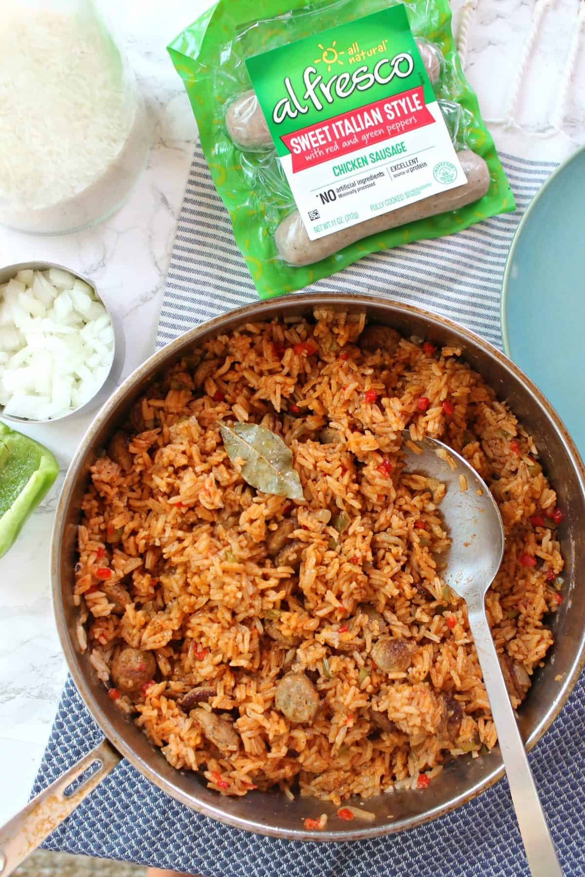 Arroz con salchicha in skillet surrounded by ingredients.