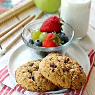 Two breakfast cookies on a small plate with a bowl of fruit on the side.