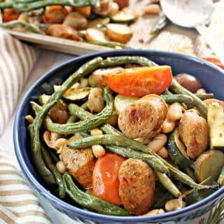 Blue bowl containing Tuscan Sheet Pan Sausage & Vegetables.