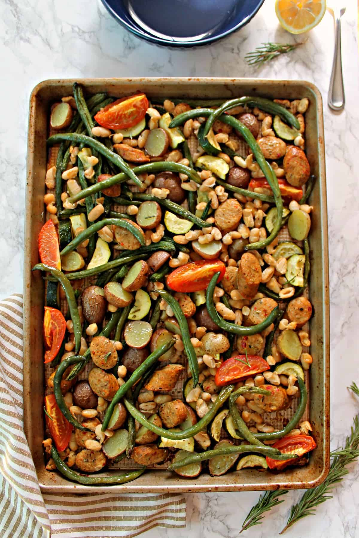 Overhead shot of Tuscan Sheet Pan Sausage & Vegetables with a striped tea towel.
