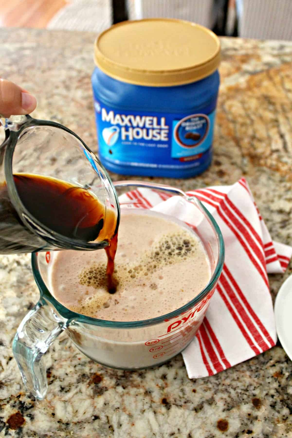 Preparation shot of brewed coffee being added to a measuring cup of milk.