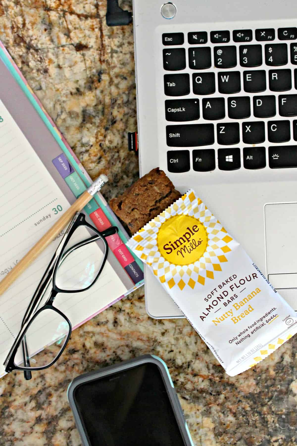 Overhead shot of Simple Mills Banana Bread Bars, laptop and glasses.