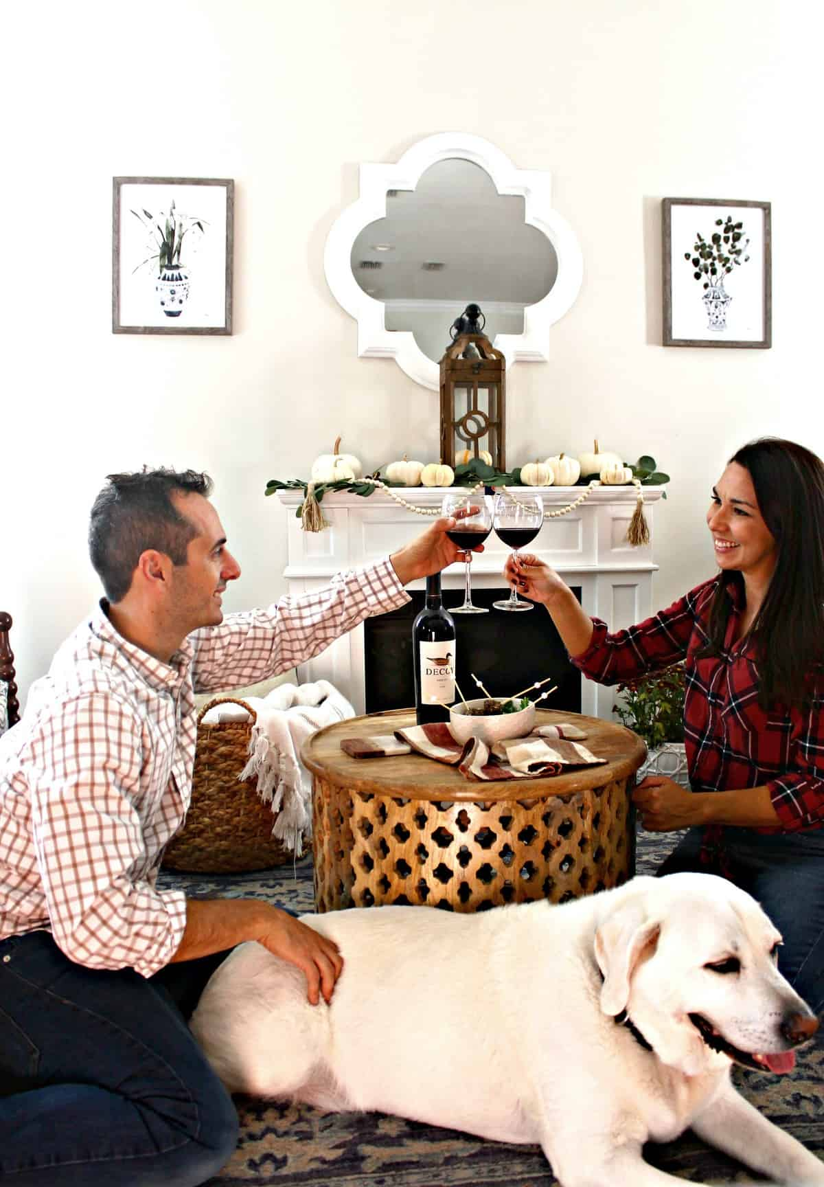 Man and woman toasting with wine in living room with dog.