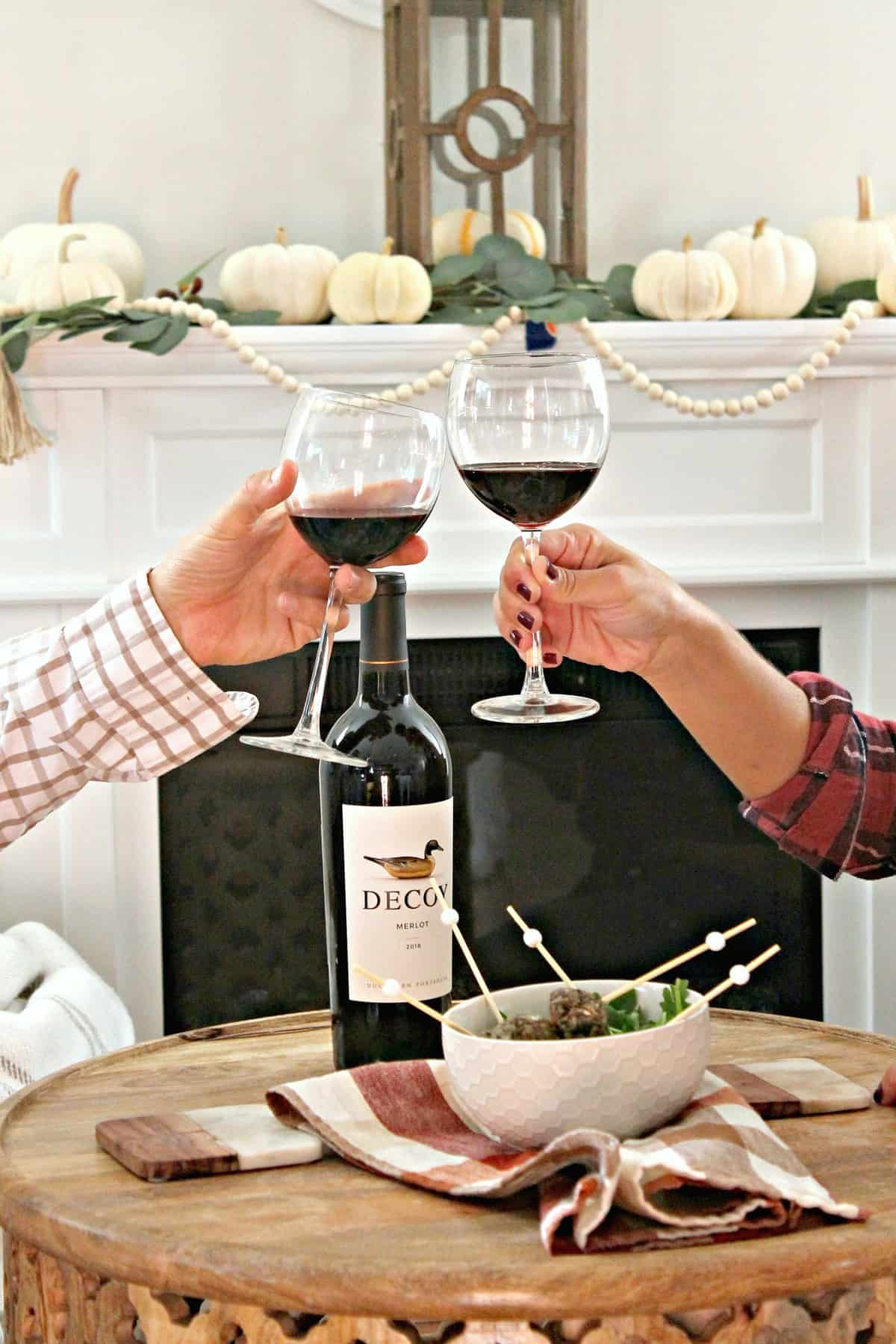 Close up of two people toasting with merlot wine in glasses.