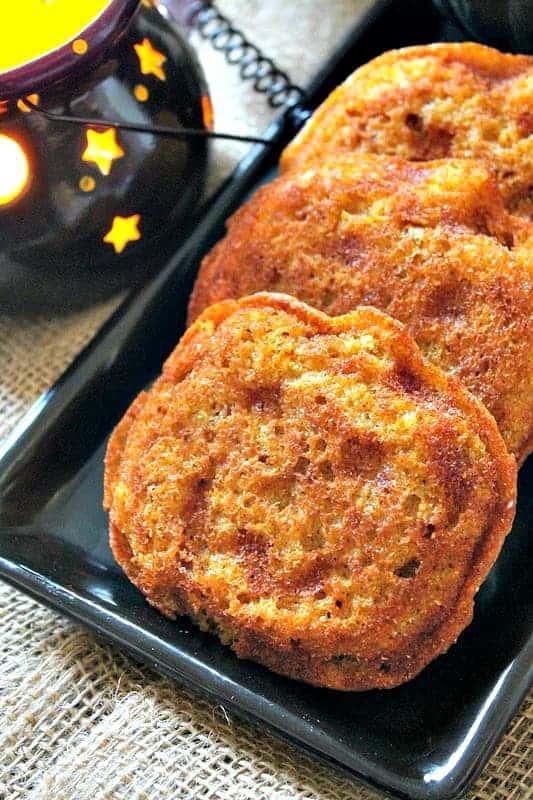 Close up of pumpkin shaped Gluten Free Pumpkin Cornbread on a black serving plate.
