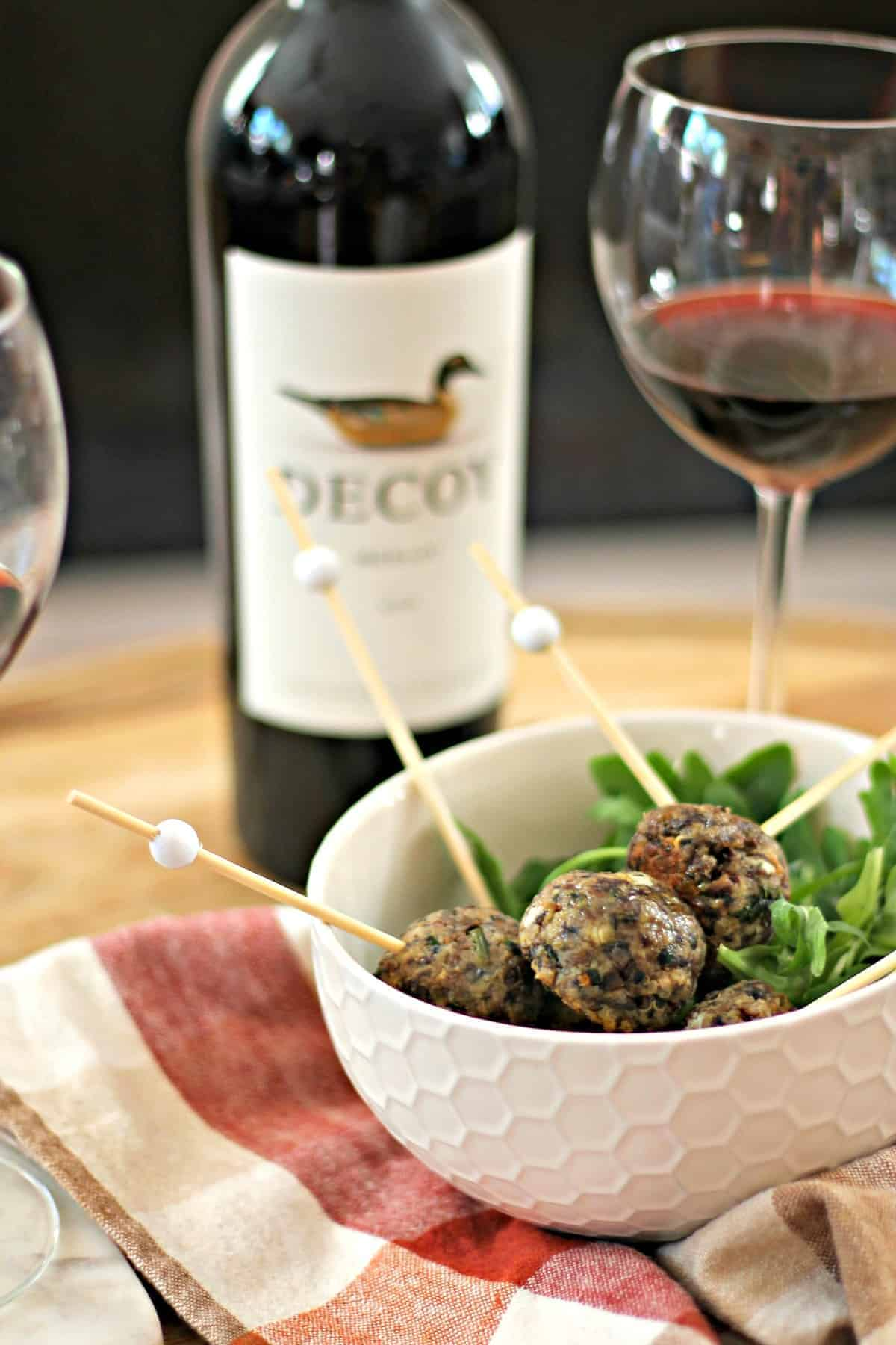 Vegetarian meatballs in a white bowl with merlot wine in the background.