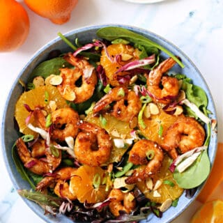 Overhead shot of Asian-Inspired Orange Salad with Shrimp with oranges next to it.