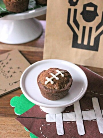 Image of a Football Pie Cookie Cup on a mini white cake plate surrounded by football party supplies.