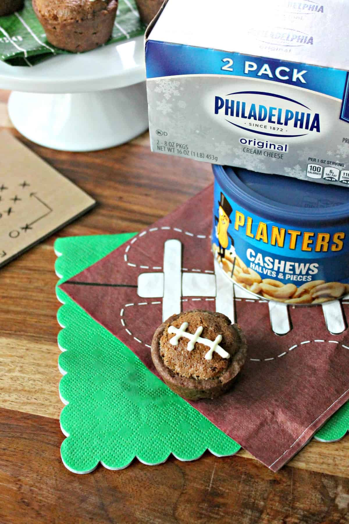 Football Pie Cookie Cup on a football napkin with can of cashews & cream cheese beside it.
