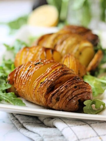 Close up shot of cooked Hasselback potato on a plate.
