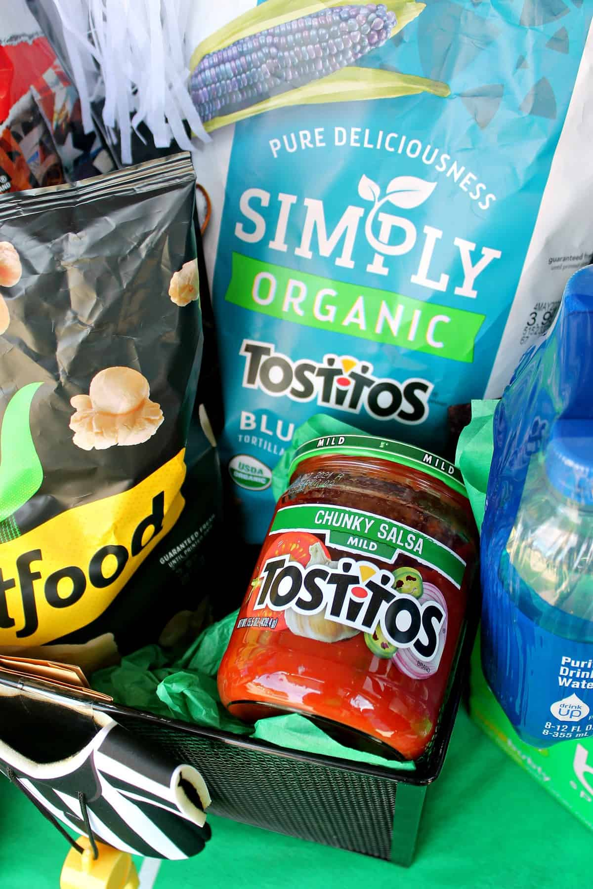 Close up of Tostitos Salsa and Simply Organic Tostitos Blue Corn Chips in tailgate setting.
