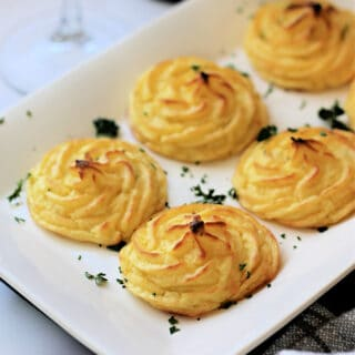 Close up of cooked Duchess Potatoes on a white serving dish.