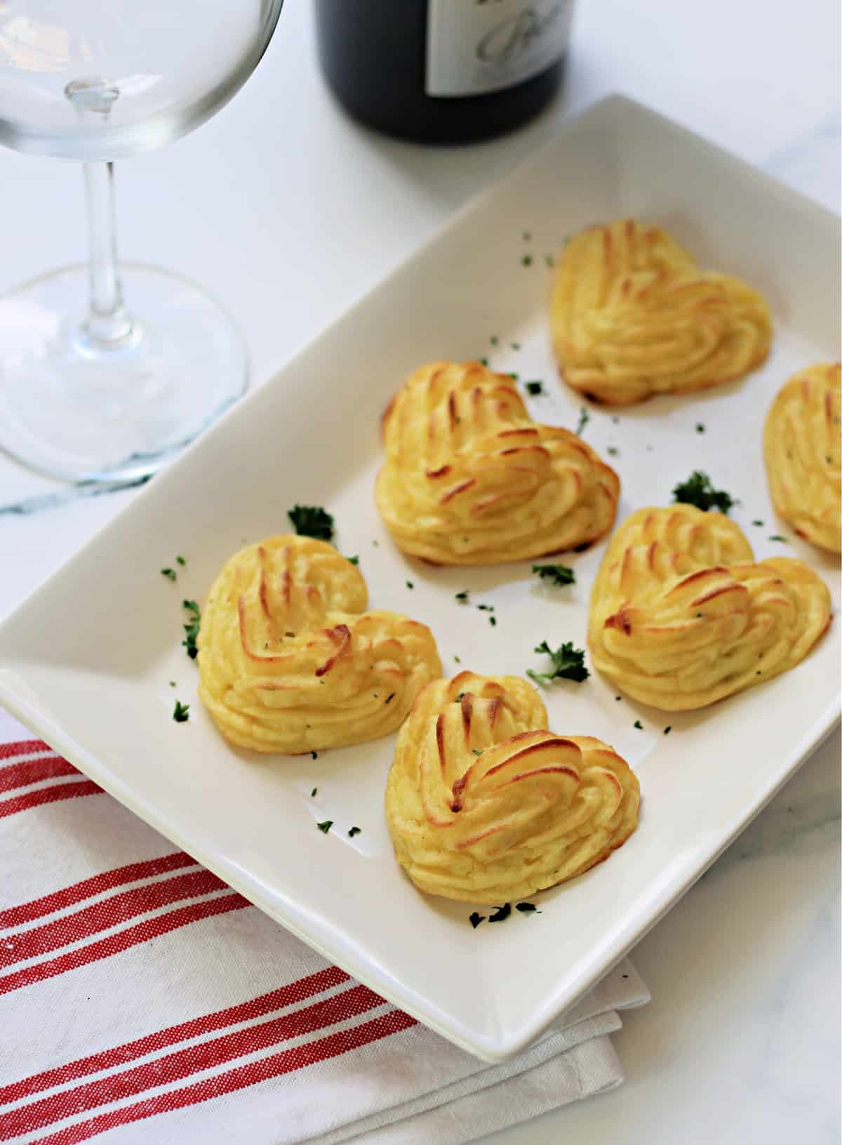 Heart-shaped Duchess Potatoes on a white serving dish.