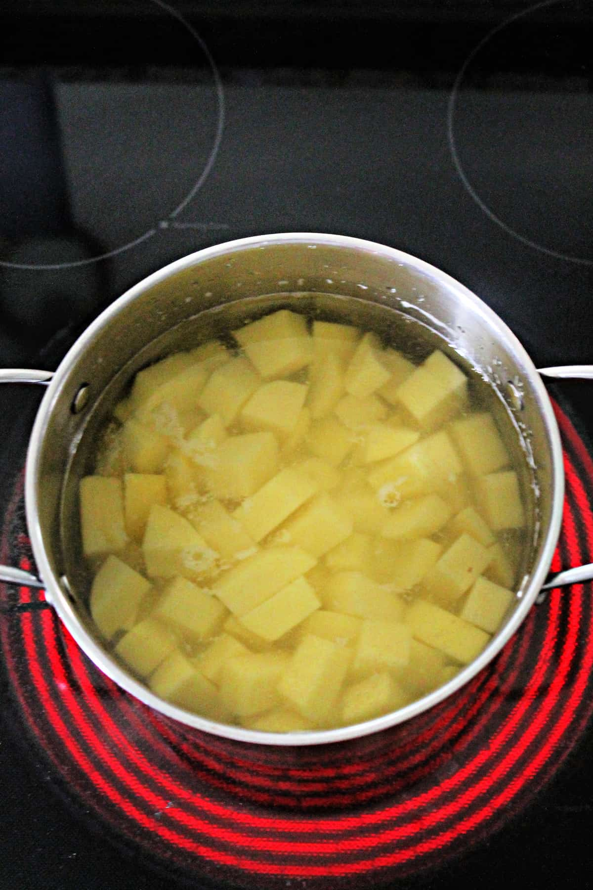 Overhead shot of diced potatoes in a pot with water on stovetop.