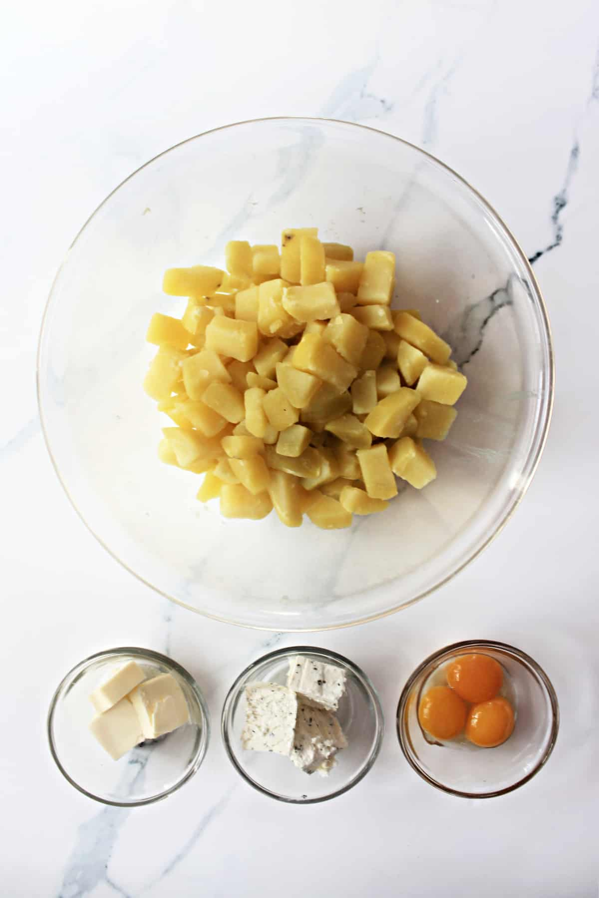 Overhead shot of ingredients for Duchess Potatoes -- cooked diced potatoes, egg yolks, Boursin cheese, and butter.