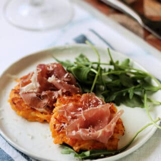 Close up of butternut squash fritters topped with proscuitto di San Daniele on an appetizer plate.