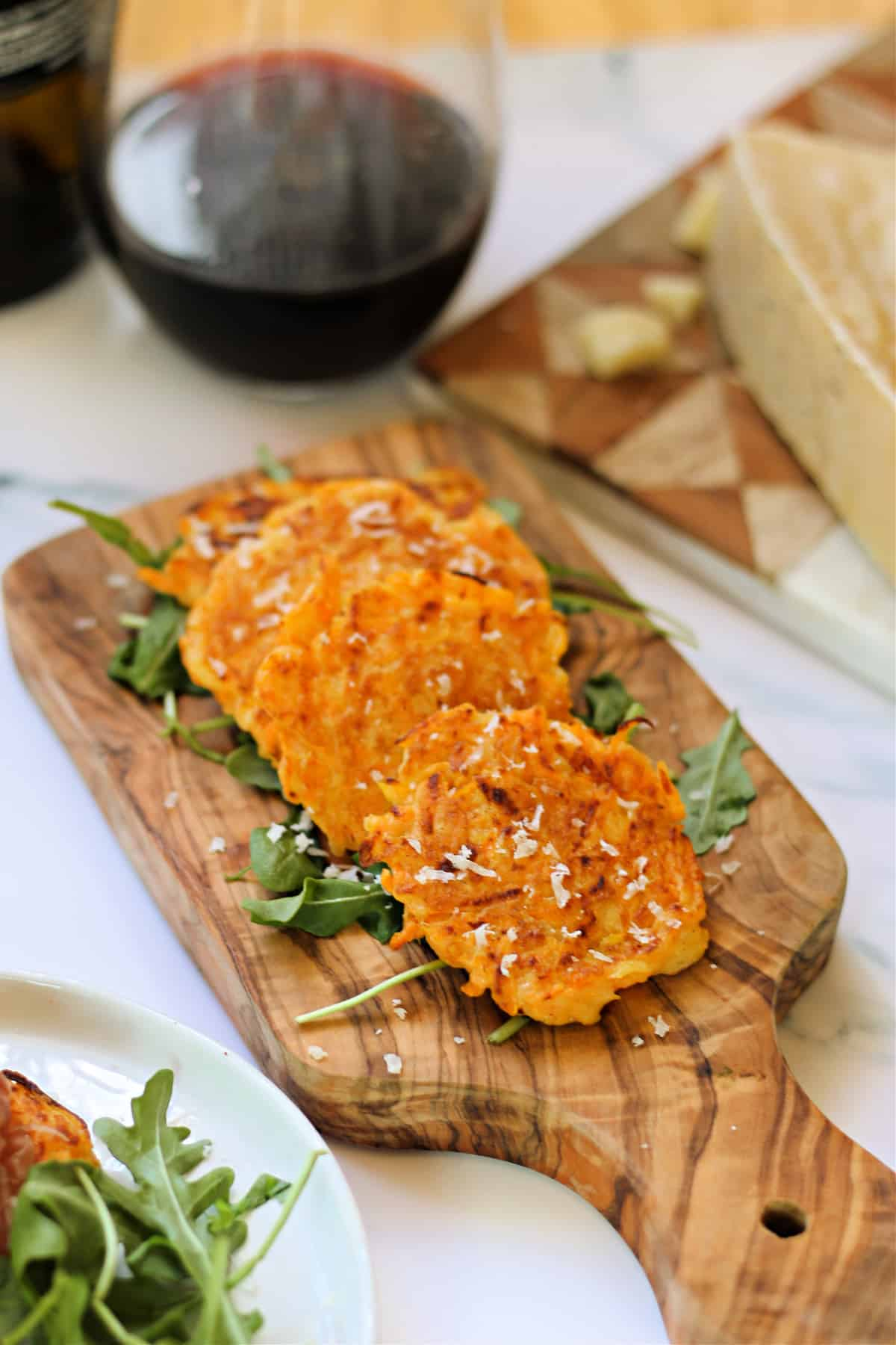 Butternut squash fritter appetizers on a small wood board.