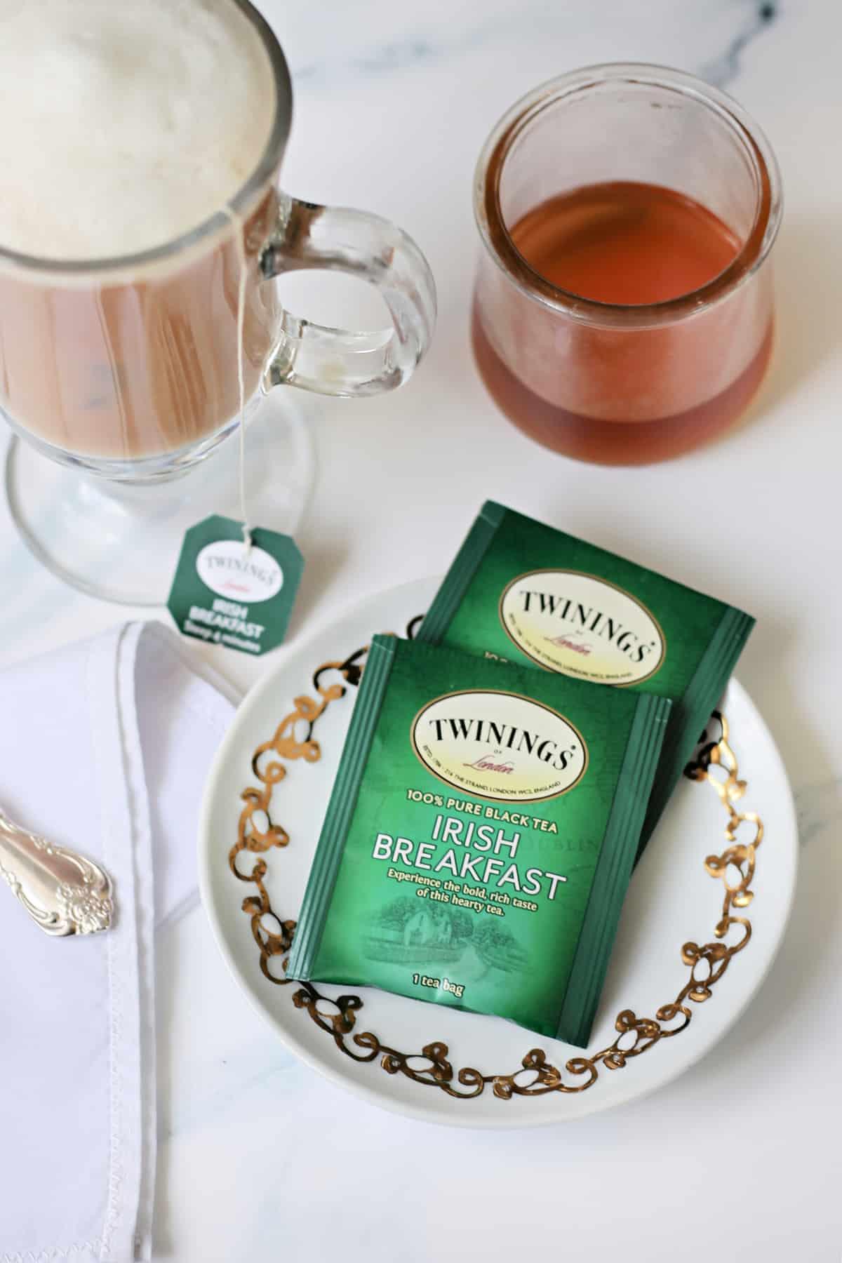 Irish Breakfast Tea bags on a small white plate next to tea latte.