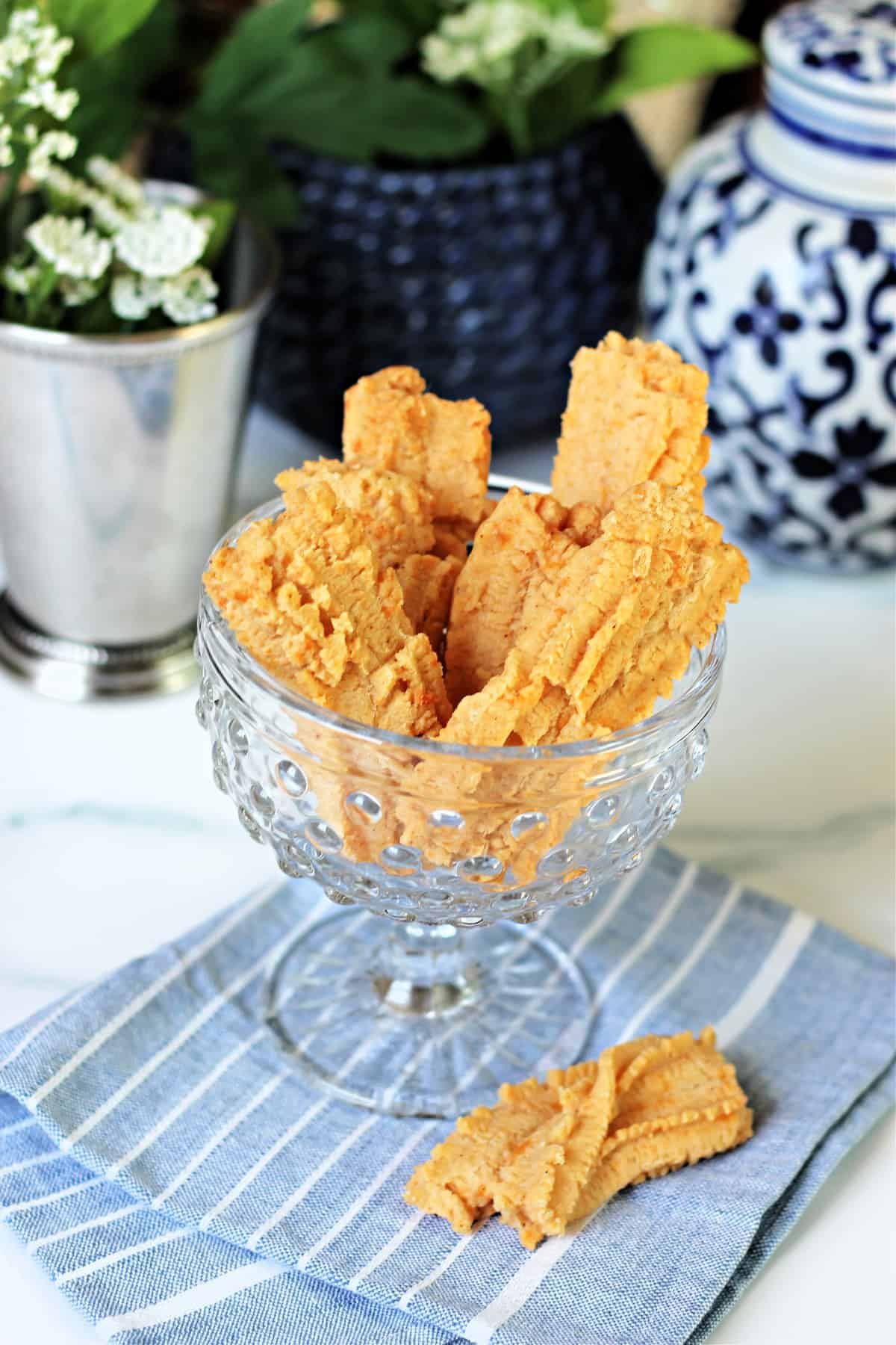 Southern Cheese Straws in a clear glass dish with decorative elements surrounding.