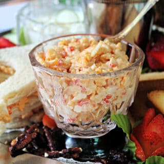 Pimento Cheese in a glass serving dish with a silver spreader.