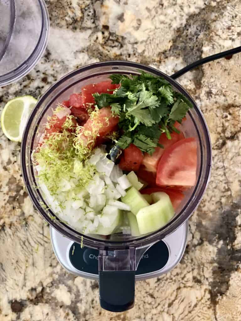 Ingredients for Grilled Watermelon Salsa in the bowl of a food processor.