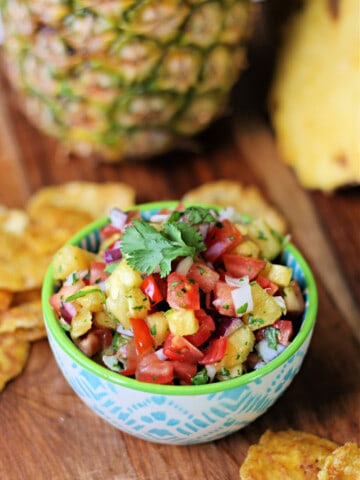 Pineapple Pico de Gallo salsa in a small bowl with plantain chips surrounding it and a pineapple in the background.