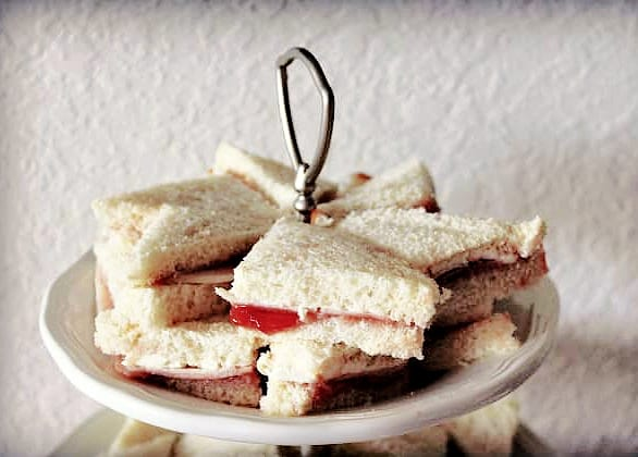 Elena Ruz finger sandwiches on the top of a white 3-tiered platter.