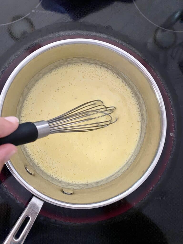 Whisking Pineapple Curd mixture in a small saucepan.