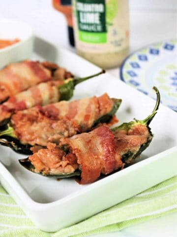 Close up of Air Fryer Jalapeno Poppers on a white platter with a lime green napkin underneath it.