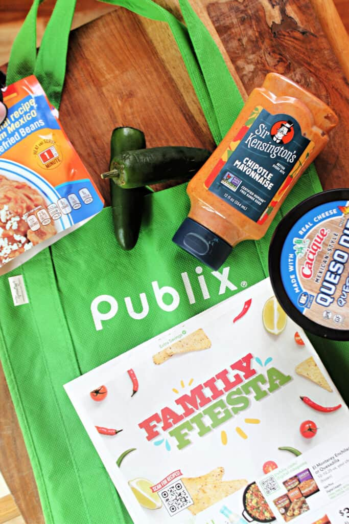 Wooden surface with a reusable Publix bag and various ingredients along with a grocery store savings flyer.