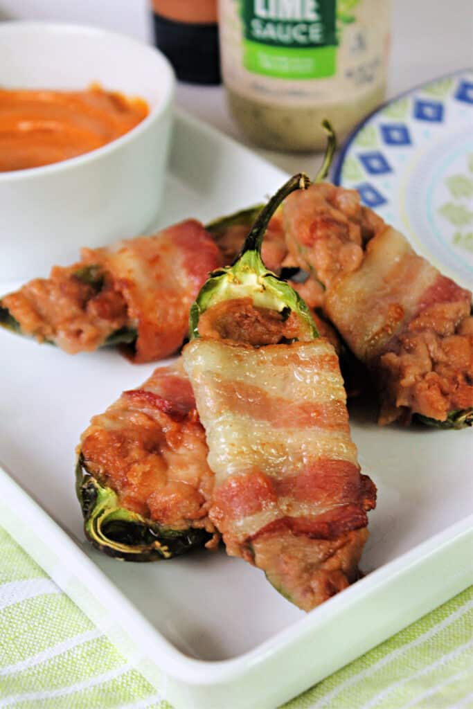 White platter of air fryer jalapeno poppers with dipping sauce in background.