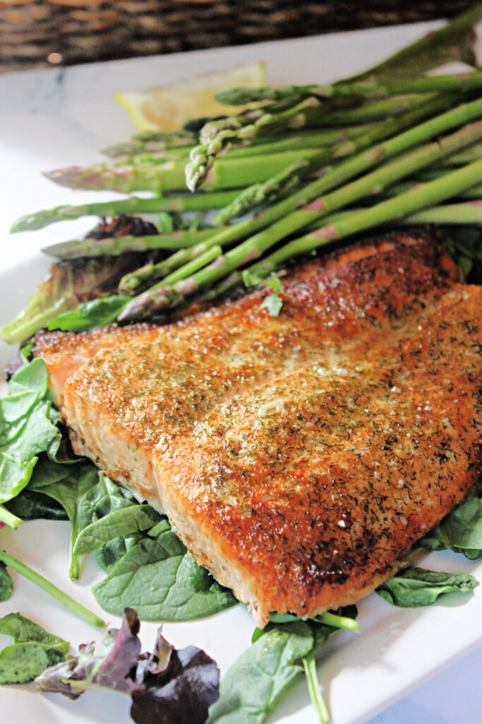 Filet of salmon cooked in the air fryer on a serving platter with asparagus.