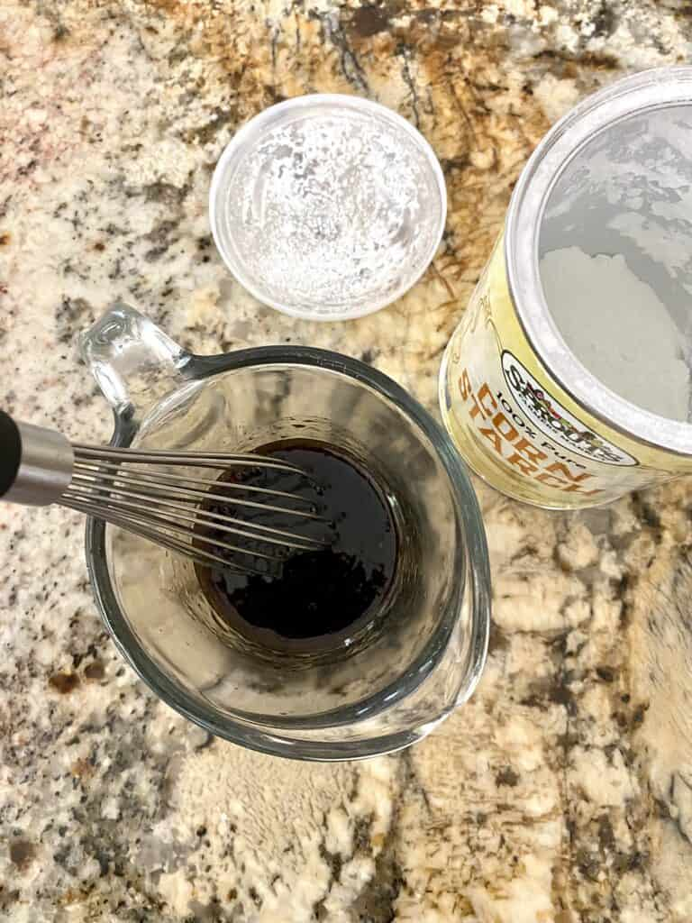 Whisking ingredients for Asian-Inspired Stuffed Pepper sauce in a clear measuring cup.
