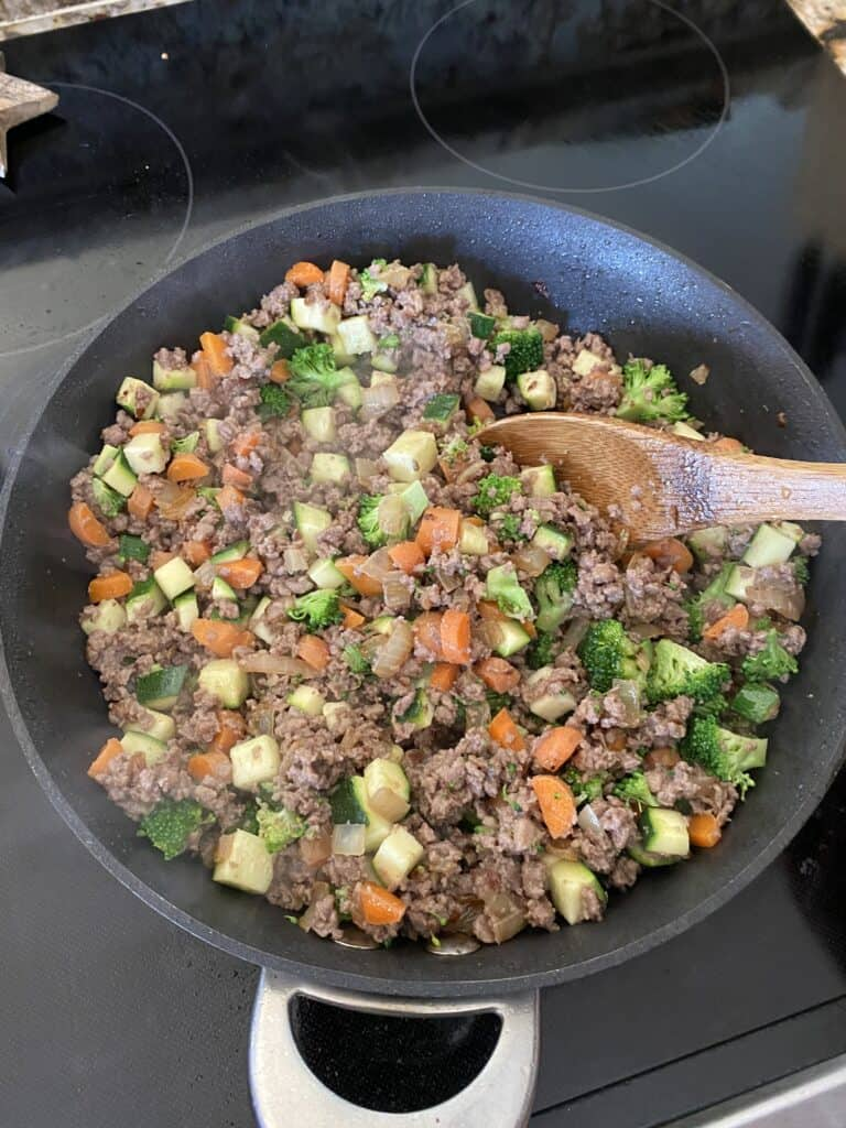 Ground turkey and vegetables cooking in a skillet for Asian Stuffed Pepper filling.