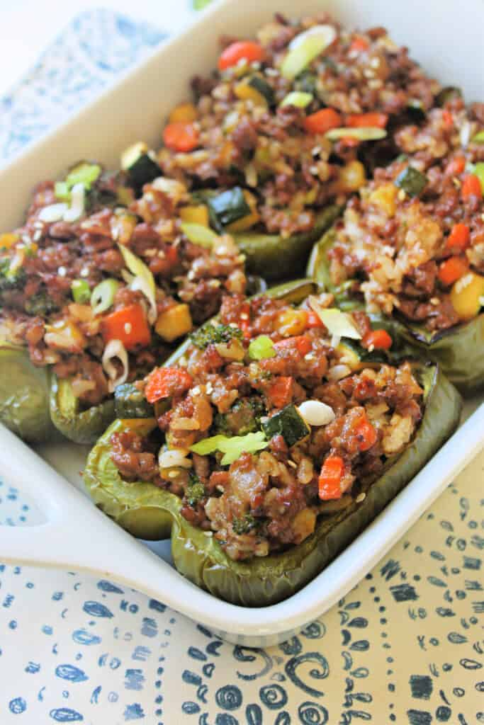 Cooked Asian-Inspired Stuffed Peppers in a white baking dish.