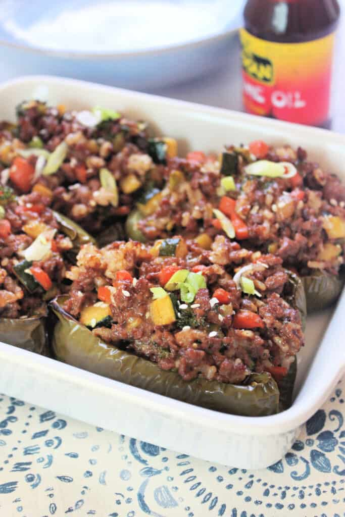 Asian-Inspired Stuffed Peppers in a white baking dish with sesame oil in the background.