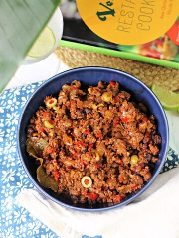 Cuban Picadillo in a blue ceramic bowl with Versaille Restaurant Cookbook in the background.