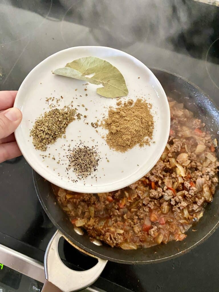 Adding bay leaf, cumin, black pepper and dried oregano to a skillet with ingredients for Cuban Picadillo.