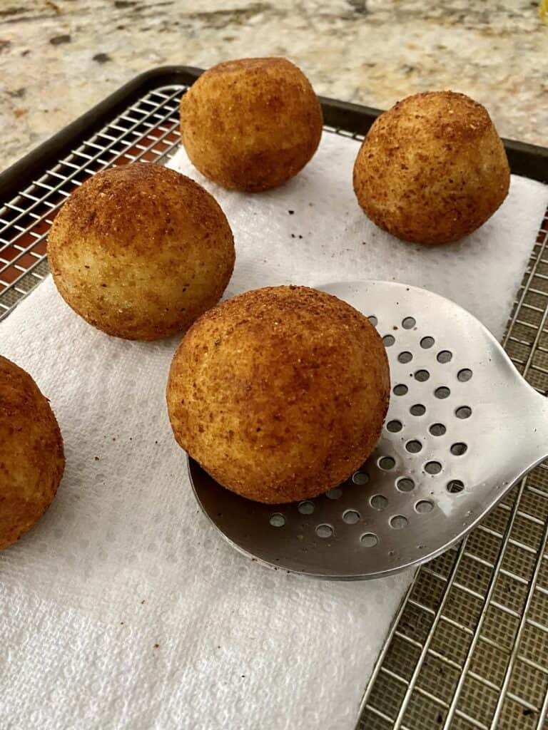 A slotted spoon placing a freshly fried Papa Rellena on a paper towel-lined cooling rack.
