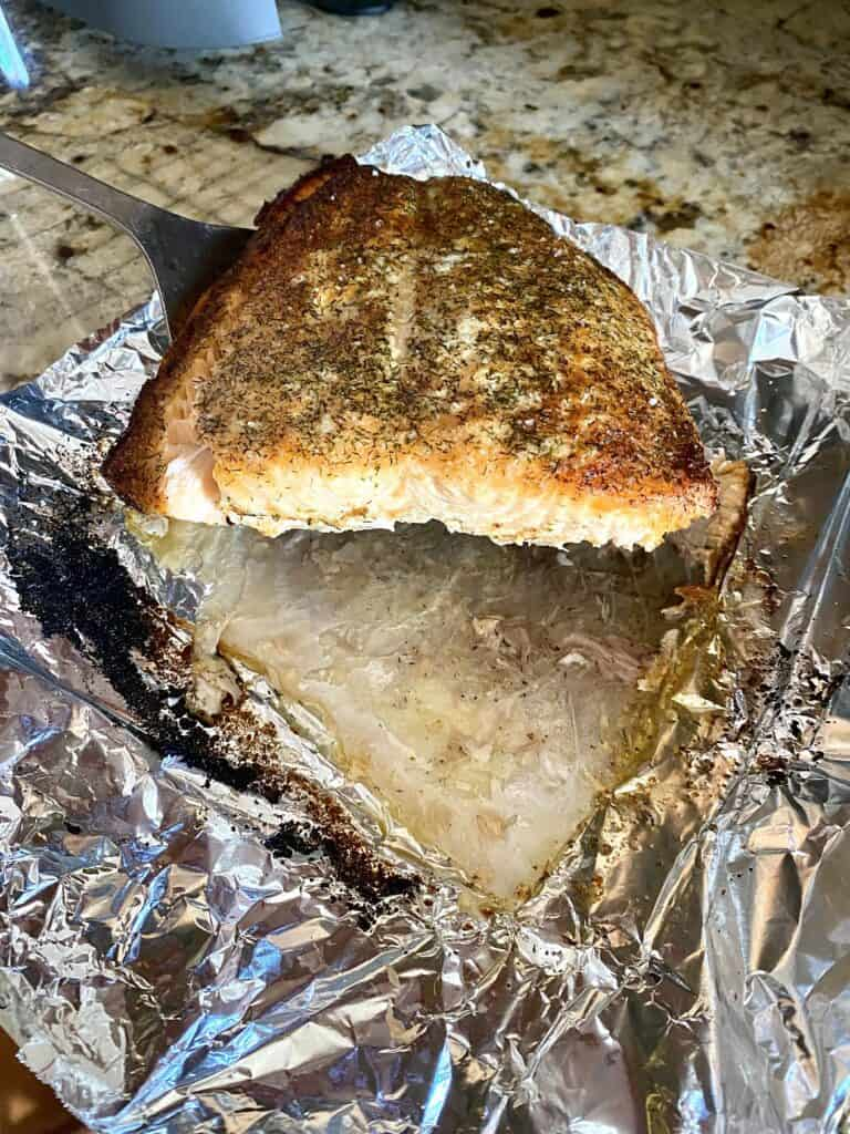Showing easy removal of salmon from skinafter cooking in air fryer on sheet of foil.